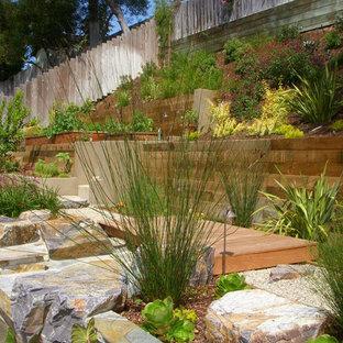 Foto på en funkis trädgård i slänt, med en stödmur