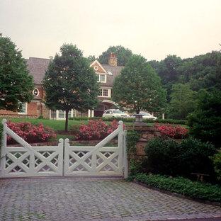 Immagine di un grande vialetto d'ingresso vittoriano davanti casa con un muro di contenimento e pavimentazioni in pietra naturale