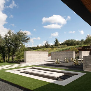 This is an example of a modern partial sun landscaping in Austin with a fire pit.