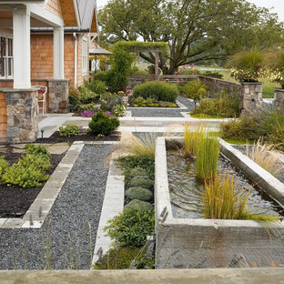 Imagen de jardín clásico, grande, en verano, en patio delantero, con fuente, exposición total al sol y adoquines de hormigón