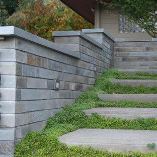 Ejemplo de jardín clásico, pequeño, en patio delantero, con exposición reducida al sol, muro de contención y adoquines de piedra natural