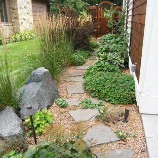 Photo of a traditional side yard stone garden path in Minneapolis.