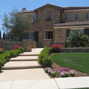 Пример оригинального дизайна: солнечный, летний участок и сад среднего размера на переднем дворе в средиземноморском стиле с подпорной стенкой, хорошей освещенностью и покрытием из каменной брусчатки