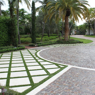 This is an example of a large modern partial sun front yard brick landscaping in Miami.