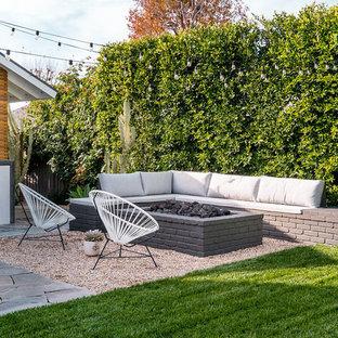 Esempio di un giardino moderno dietro casa con un focolare e ghiaia