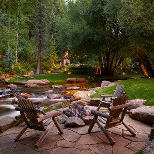 Geräumiger Rustikaler Garten im Sommer, hinter dem Haus mit Feuerstelle, Natursteinplatten und direkter Sonneneinstrahlung in Denver