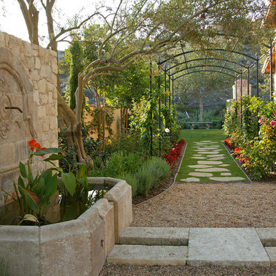 This is an example of a mediterranean full sun backyard stone formal garden in New York for spring.