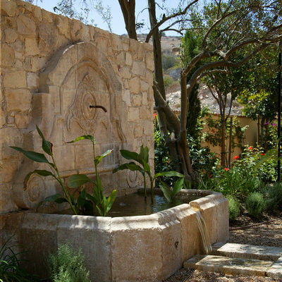 Inspiration for a large mediterranean full sun backyard stone landscaping in Orange County.