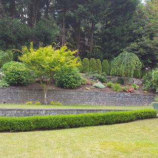 Immagine di un grande giardino tradizionale esposto in pieno sole dietro casa con un muro di contenimento e pacciame