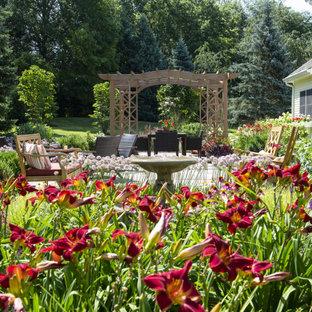 На фото: большой солнечный, летний участок и сад на заднем дворе в классическом стиле с освещенностью и покрытием из каменной брусчатки с