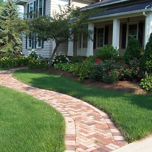 Photo of a mid-sized traditional full sun front yard brick garden path in Cleveland for summer.