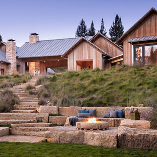 This is an example of a huge farmhouse full sun backyard stone landscaping in San Francisco with a fire pit.