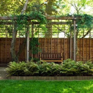 Modern inredning av en mellanstor trädgård i skuggan, med en vertikal trädgård och marksten i tegel på hösten