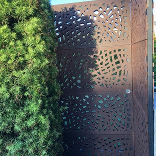 Cette image montre un xéropaysage avant minimaliste de taille moyenne avec un portail, une exposition partiellement ombragée et du gravier.