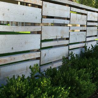 Réalisation d'un petit jardin avec une terrasse en bois ou composite avant design l'hiver avec un mur de soutènement et une exposition ensoleillée.