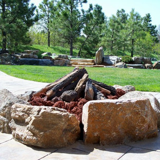 Design ideas for a mid-sized rustic full sun backyard concrete paver landscaping in Denver with a fire pit.