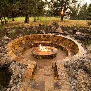 Exemple d'un grand jardin arrière craftsman avec un foyer extérieur, une exposition ensoleillée et des pavés en pierre naturelle.