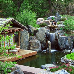 Asiatischer Garten mit Wasserspiel und Dielen in Denver