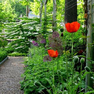 Foto di un piccolo giardino formale tradizionale esposto a mezz'ombra davanti casa in primavera con ghiaia e un ingresso o sentiero