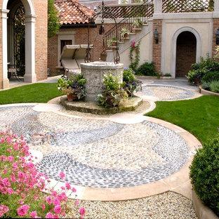 Ejemplo de jardín francés, mediterráneo, en verano, en patio, con adoquines de piedra natural