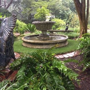 Design ideas for a mid-sized traditional shade courtyard stone water fountain landscape in Raleigh.