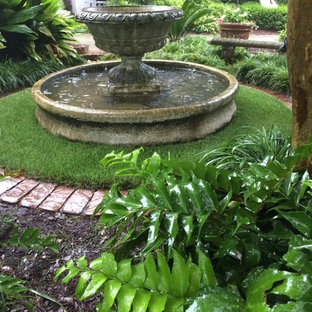 Photo of a mid-sized traditional shade courtyard stone water fountain landscape in Raleigh.