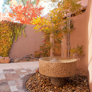 Photo of a large courtyard partial sun garden for fall in Albuquerque with a water feature and concrete pavers.
