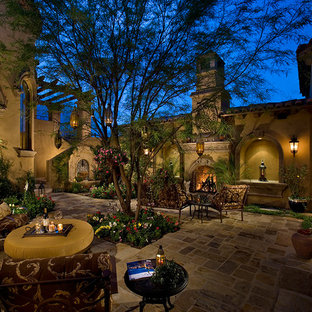 This is an example of an expansive traditional courtyard full sun formal garden in Phoenix with a water feature and natural stone pavers.