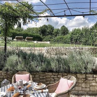 Cette image montre un jardin arrière avec un mur de soutènement et du gravier.