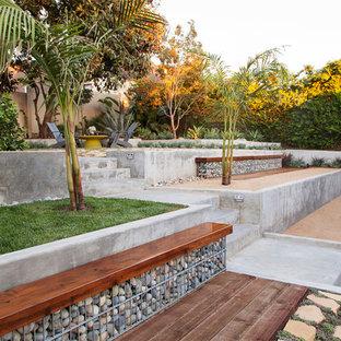 Cette image montre un jardin arrière design avec un mur de soutènement, une exposition partiellement ombragée et du gravier.