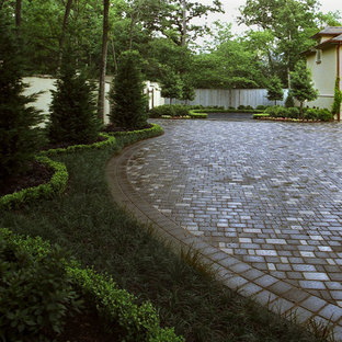 This is an example of a mid-sized traditional full sun front yard concrete paver driveway in Houston for fall.