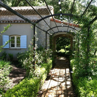 Inspiration for a farmhouse shade backyard brick landscaping in Sacramento.