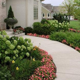 На фото: большие участки и сады на переднем дворе в классическом стиле с мощением тротуарной плиткой