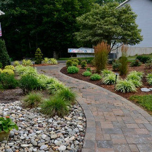 This is an example of a large classic back partial sun garden for spring in DC Metro with a garden path and natural stone paving.