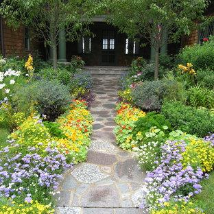 Réalisation d'un jardin avant victorien l'été avec des pavés en pierre naturelle.