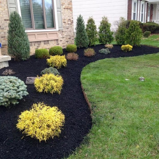 This is an example of a mid-sized traditional full sun front yard formal garden in New York for summer.