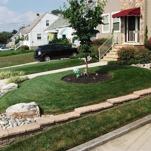 Inspiration for a mid-sized traditional full sun front yard concrete paver retaining wall landscape in Philadelphia for summer.