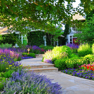 Idée de décoration pour un jardin avant tradition l'été avec une exposition partiellement ombragée et un massif de fleurs.