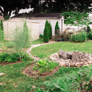Photo of a mid-sized transitional full sun backyard stone landscaping in Toronto for summer.
