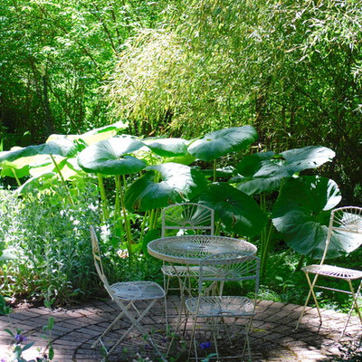Photo of a mid-sized eclectic shade backyard brick formal garden in Seattle for summer.