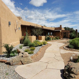 Design ideas for a large southwestern drought-tolerant and partial sun front yard gravel landscaping in Albuquerque.