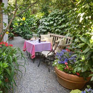 Foto de jardín ecléctico con gravilla y privacidad