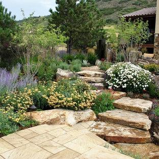 Ejemplo de camino de jardín de secano, mediterráneo, en verano, en ladera, con exposición total al sol y adoquines de piedra natural