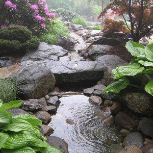 Cette image montre un jardin arrière traditionnel avec une exposition ombragée, des pavés en pierre naturelle et un point d'eau.