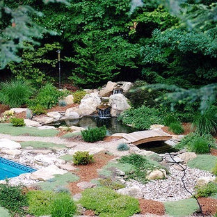 This is an example of a traditional backyard stone water fountain landscape in Miami.