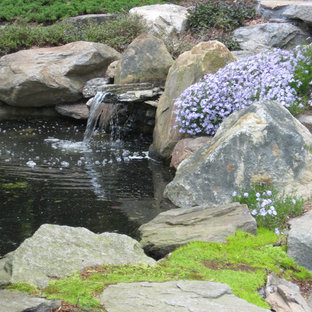 This is an example of a traditional shade backyard stone water fountain landscape in Bridgeport.