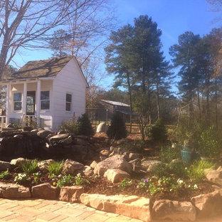 Inspiration for a mid-sized farmhouse full sun backyard river rock landscaping in Atlanta for summer.