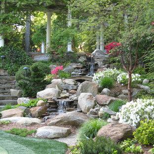 Aménagement d'un grand jardin arrière classique au printemps avec une exposition partiellement ombragée, des pavés en pierre naturelle et une cascade.