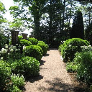 Immagine di un grande giardino vittoriano esposto a mezz'ombra dietro casa in primavera con pavimentazioni in pietra naturale e un ingresso o sentiero
