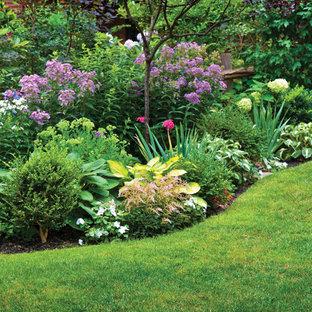 Inspiration pour un jardin à la française avant traditionnel de taille moyenne et au printemps avec une exposition partiellement ombragée, un paillis et un massif de fleurs.